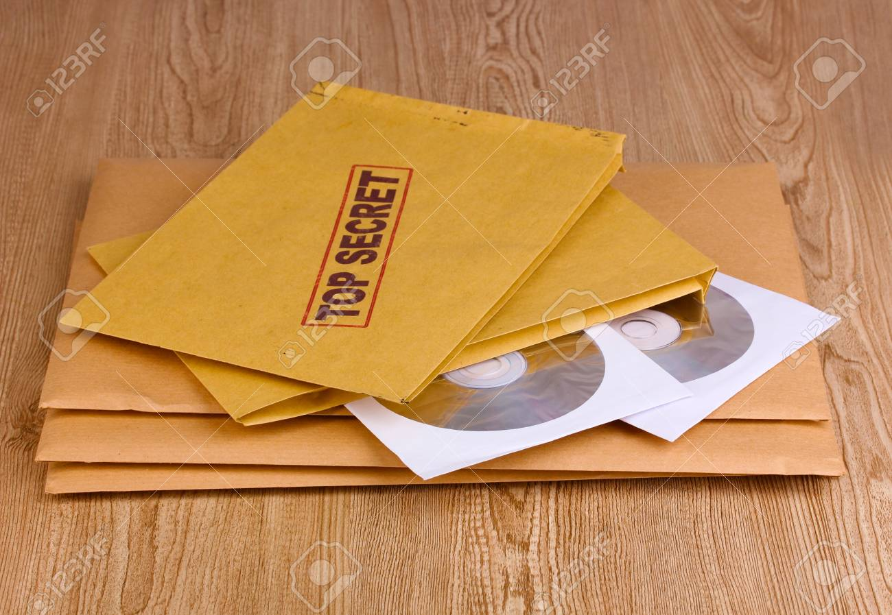 Envelopes with top secret stamp with CD disks on wooden background Stock Photo - 12310625