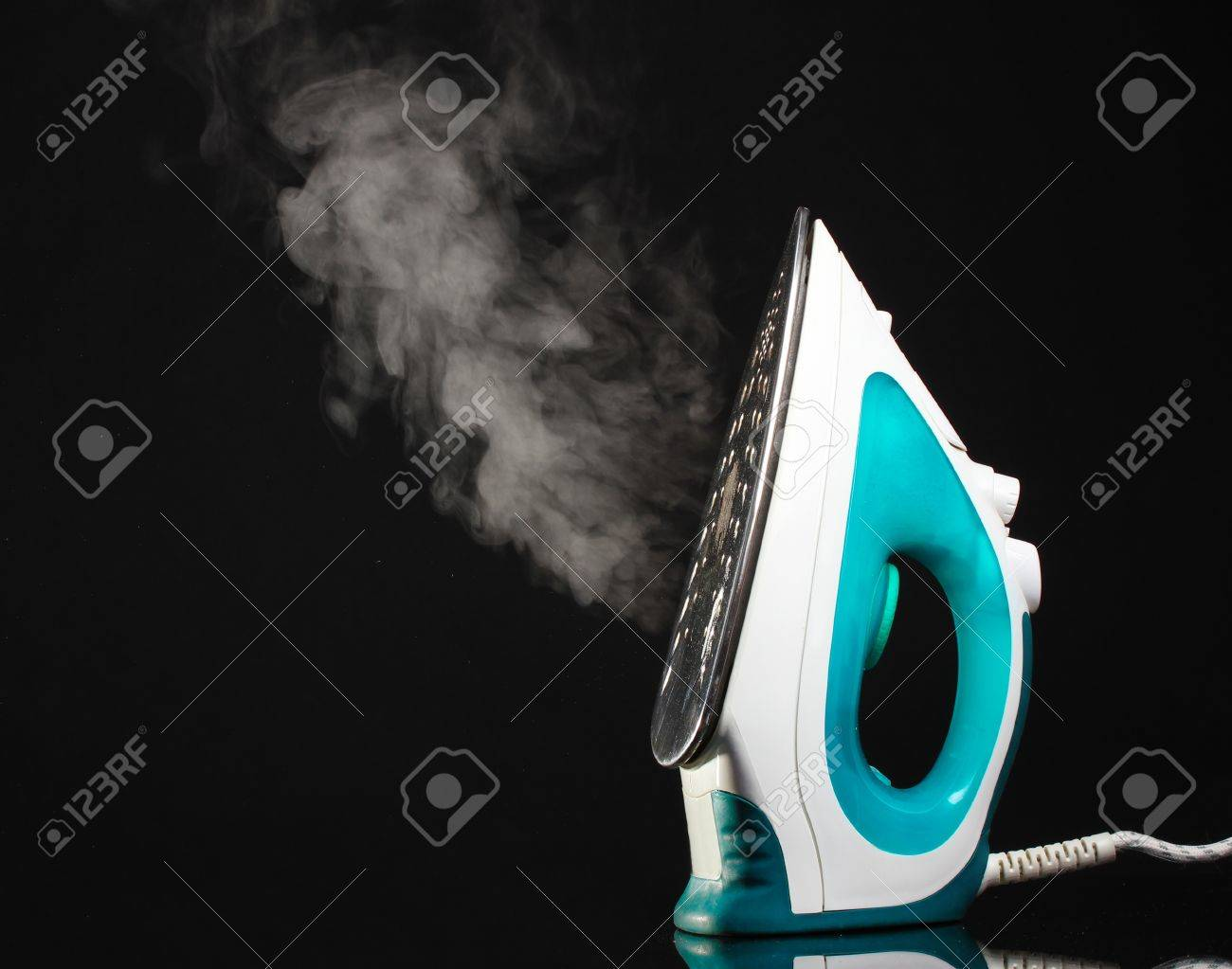Electric iron with steam on black Stock Photo - 12439650