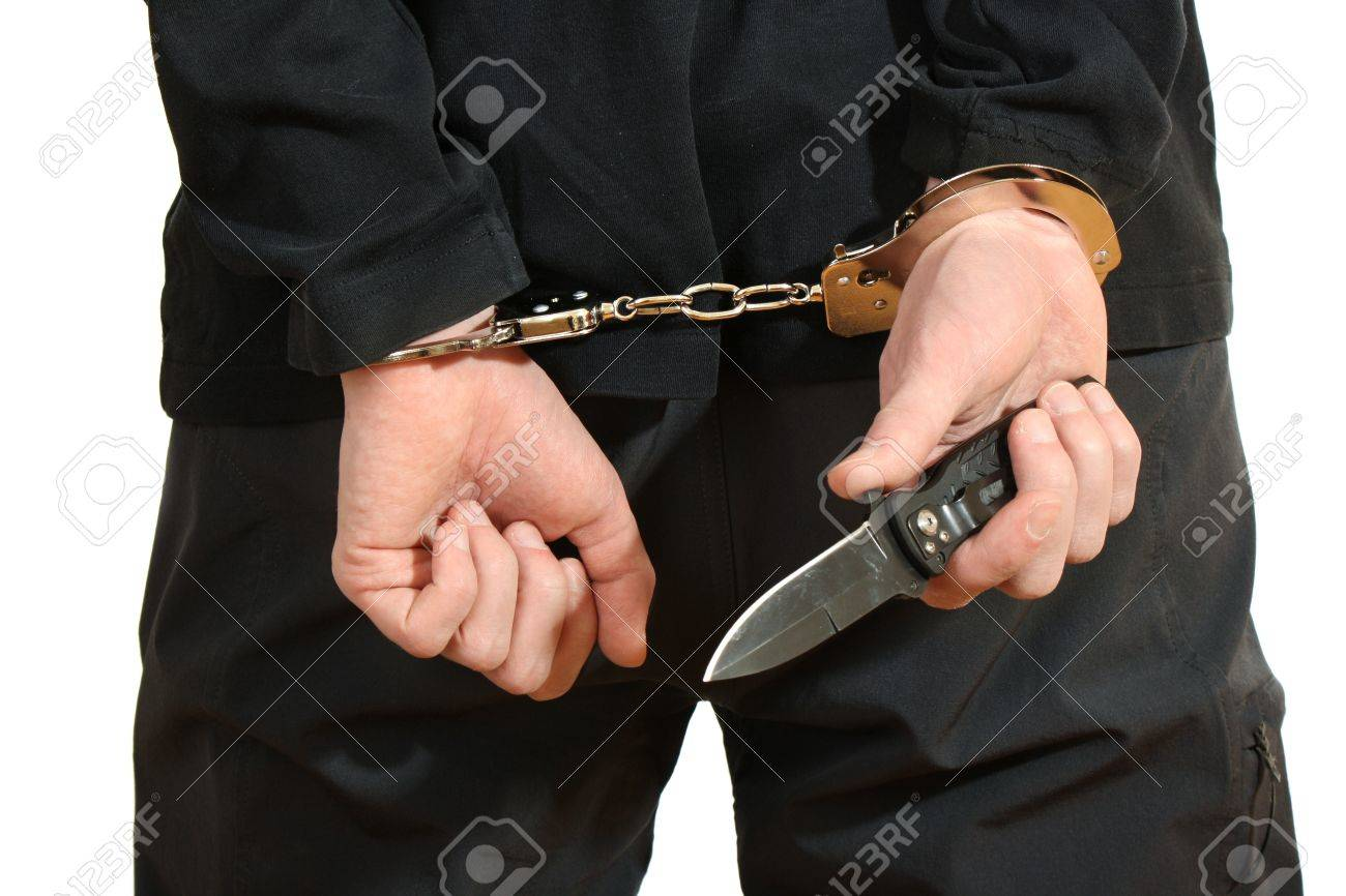 Bandit in black mask handcuffed isolated on white Stock Photo - 12564447