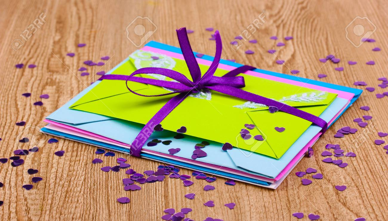 Bunch of color envelopes with ribbon and confetti on wooden background Stock Photo - 12915050