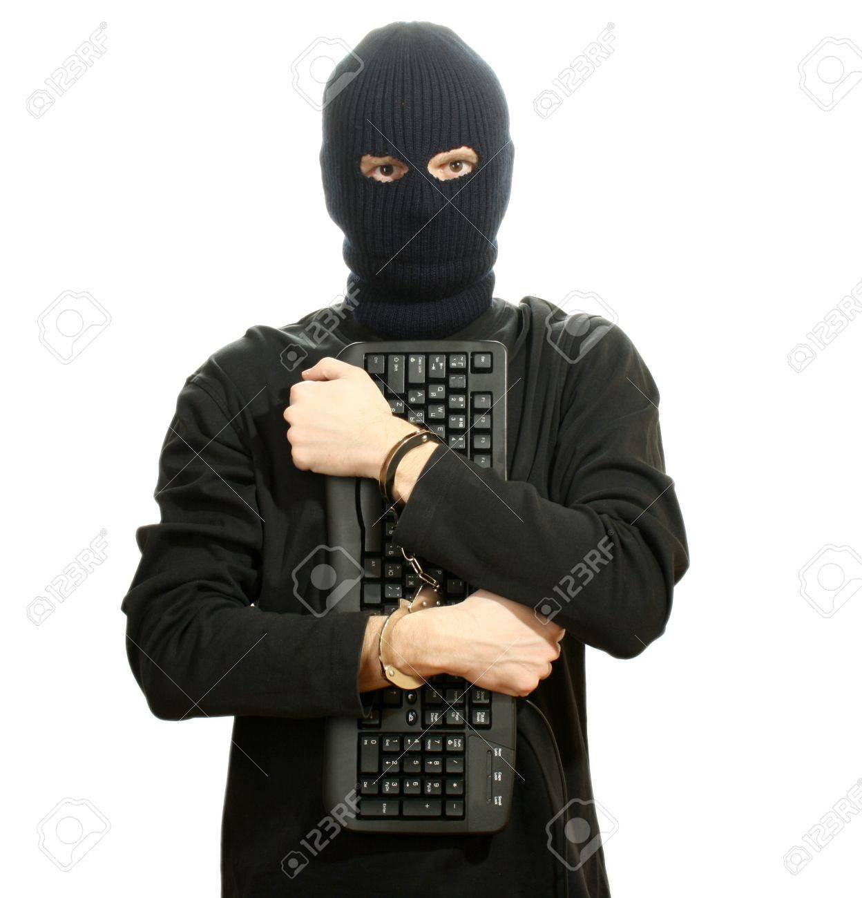 Hacker in black mask in handcuffs with keyboard isolated on white Stock Photo - 13082351