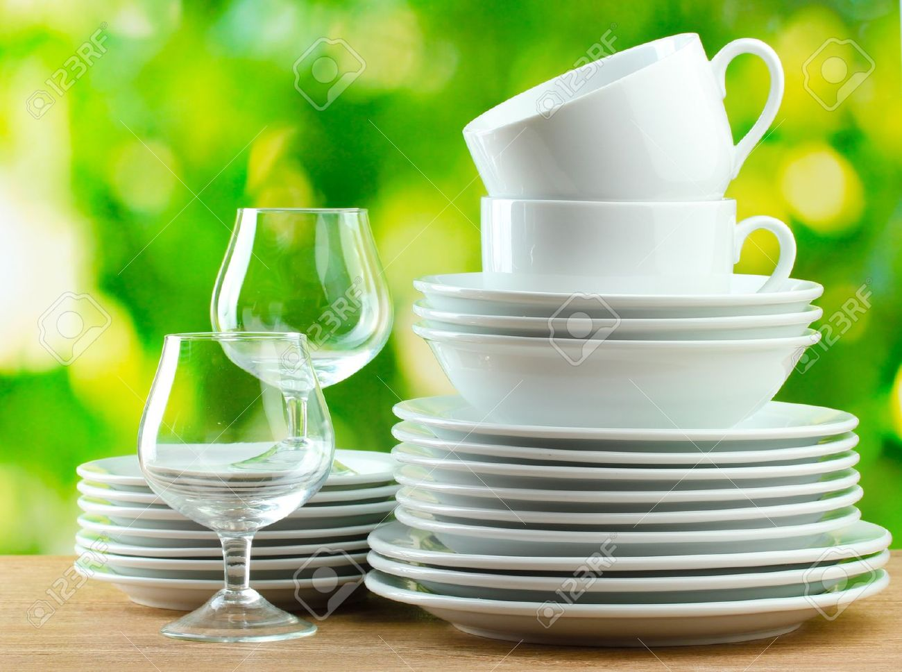 clean dishes on wooden table on green background stock photo