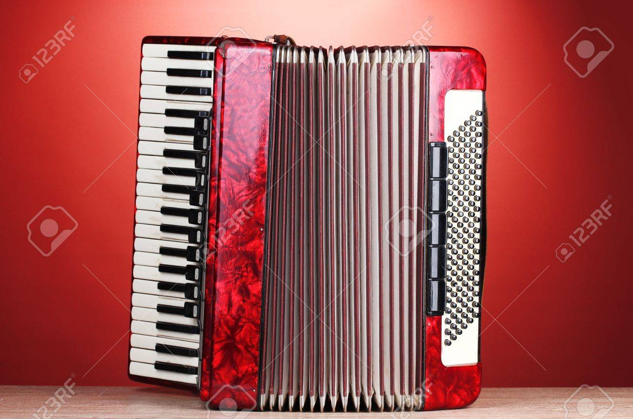 Retro accordion on wooden table on red background Stock Photo - 13084946
