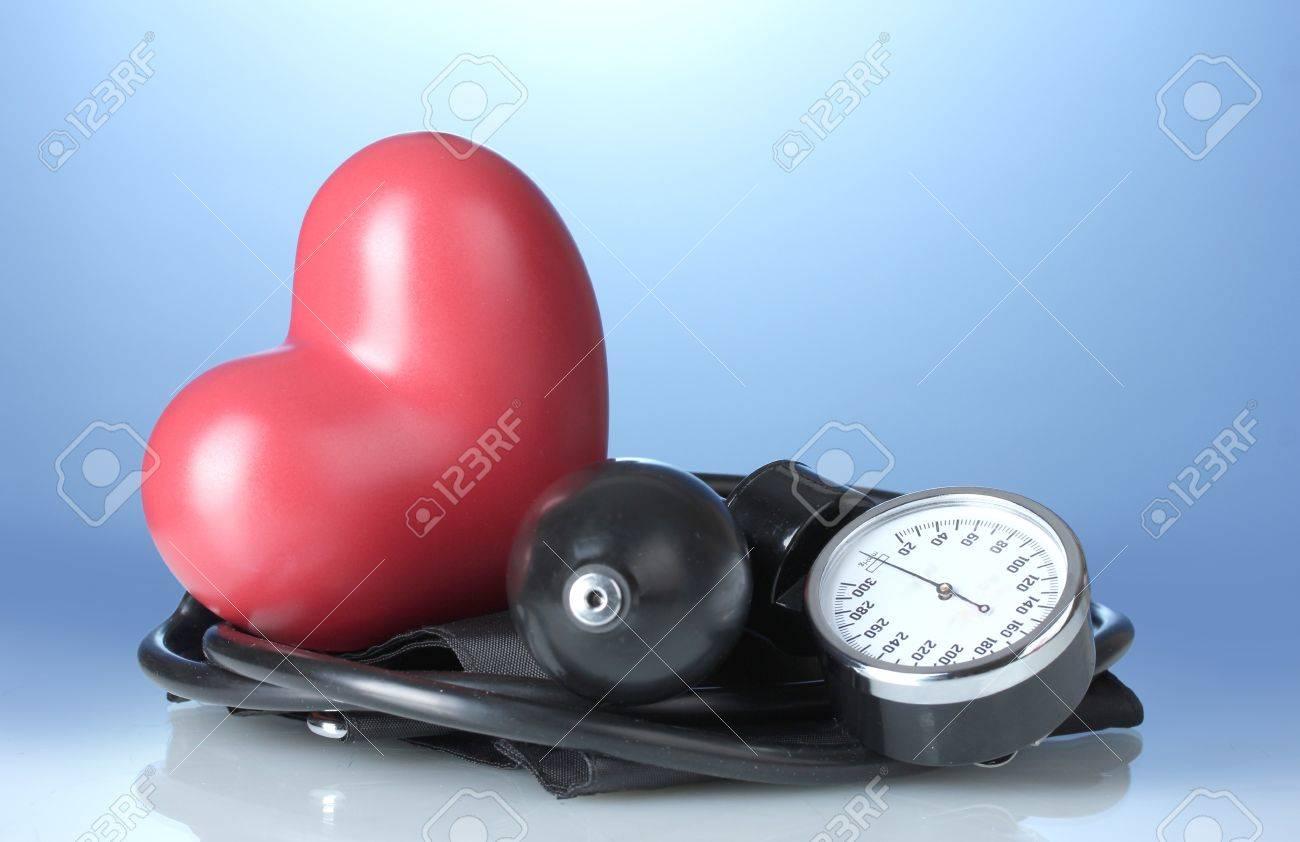 Black tonometer and heart on blue background Stock Photo - 13178944