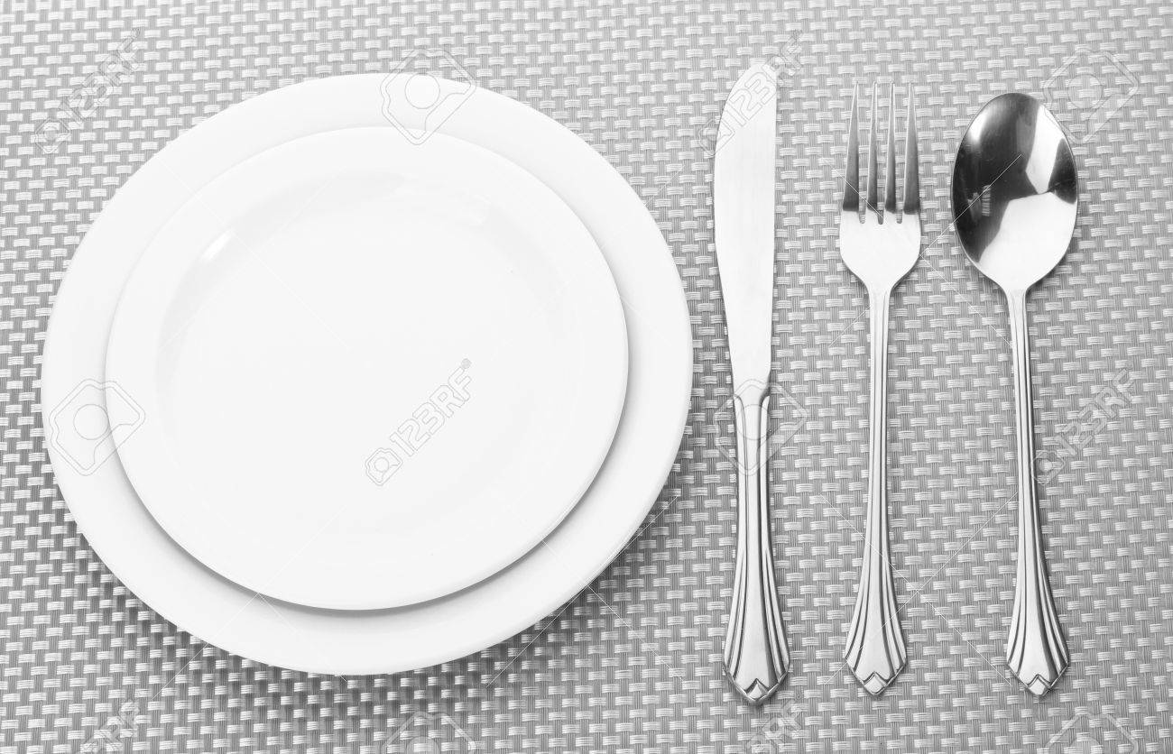 An empty white dish with knife and fork on a table - White Empty Plates With Fork Spoon And Knife On A Grey Tablecloth Stock Photo