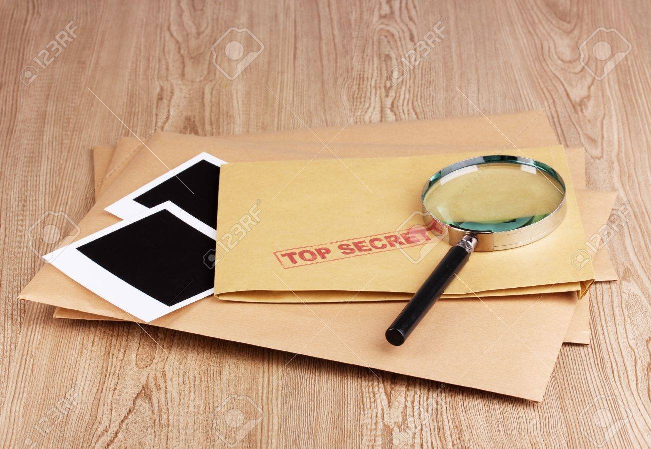 Envelopes with top secret stamp with photo papers and magnifying glass on wooden background Stock Photo - 13265388