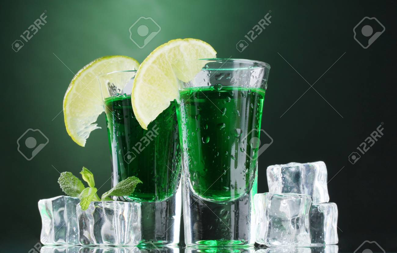 Two glasses of absinthe, lime and ice on green background Stock Photo - 13265425