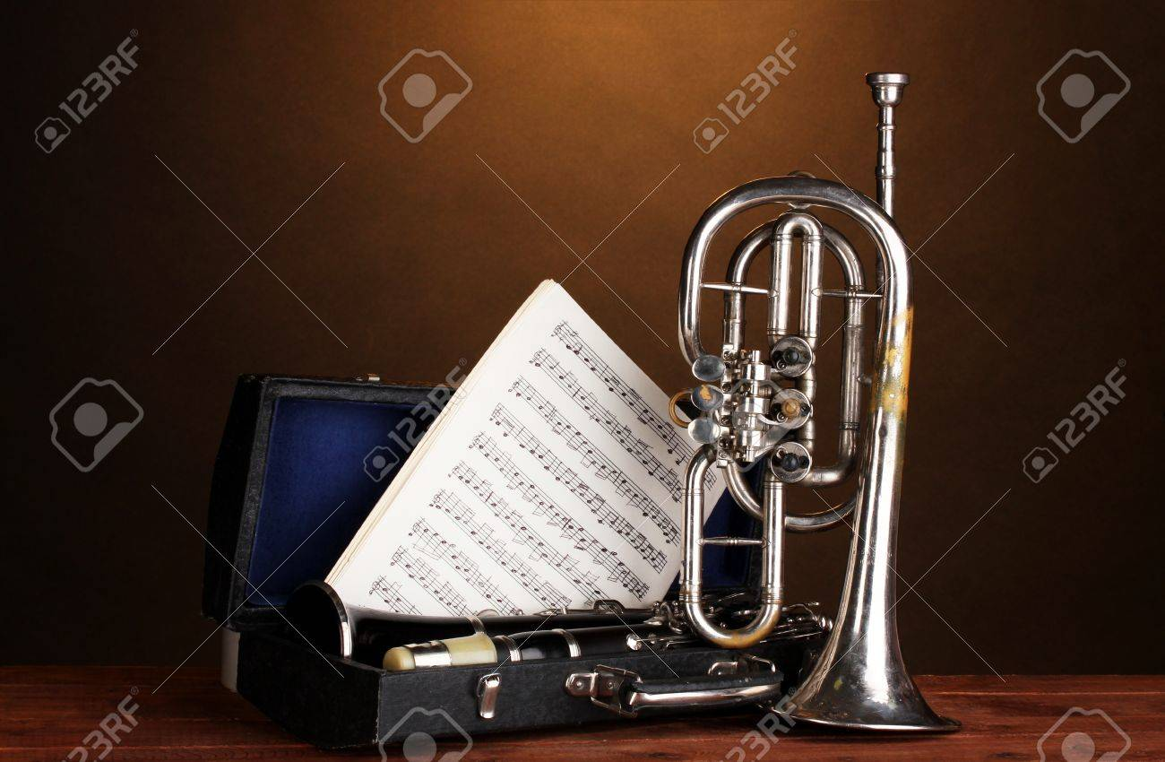 antique trumpet and clarinet in case on wooden table on brown background Stock Photo - 13373797