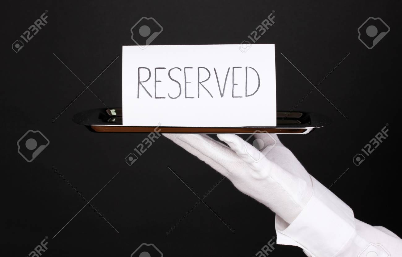 Hand in glove holding silver tray with card saying reserved isolated on black Stock Photo - 13517619