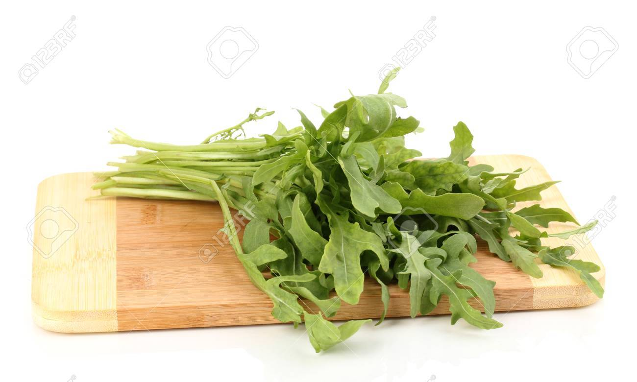 Fresh Rucola Salad Or Rocket Lettuce Leaves On Wooden Board Isolated On White Stock Photo