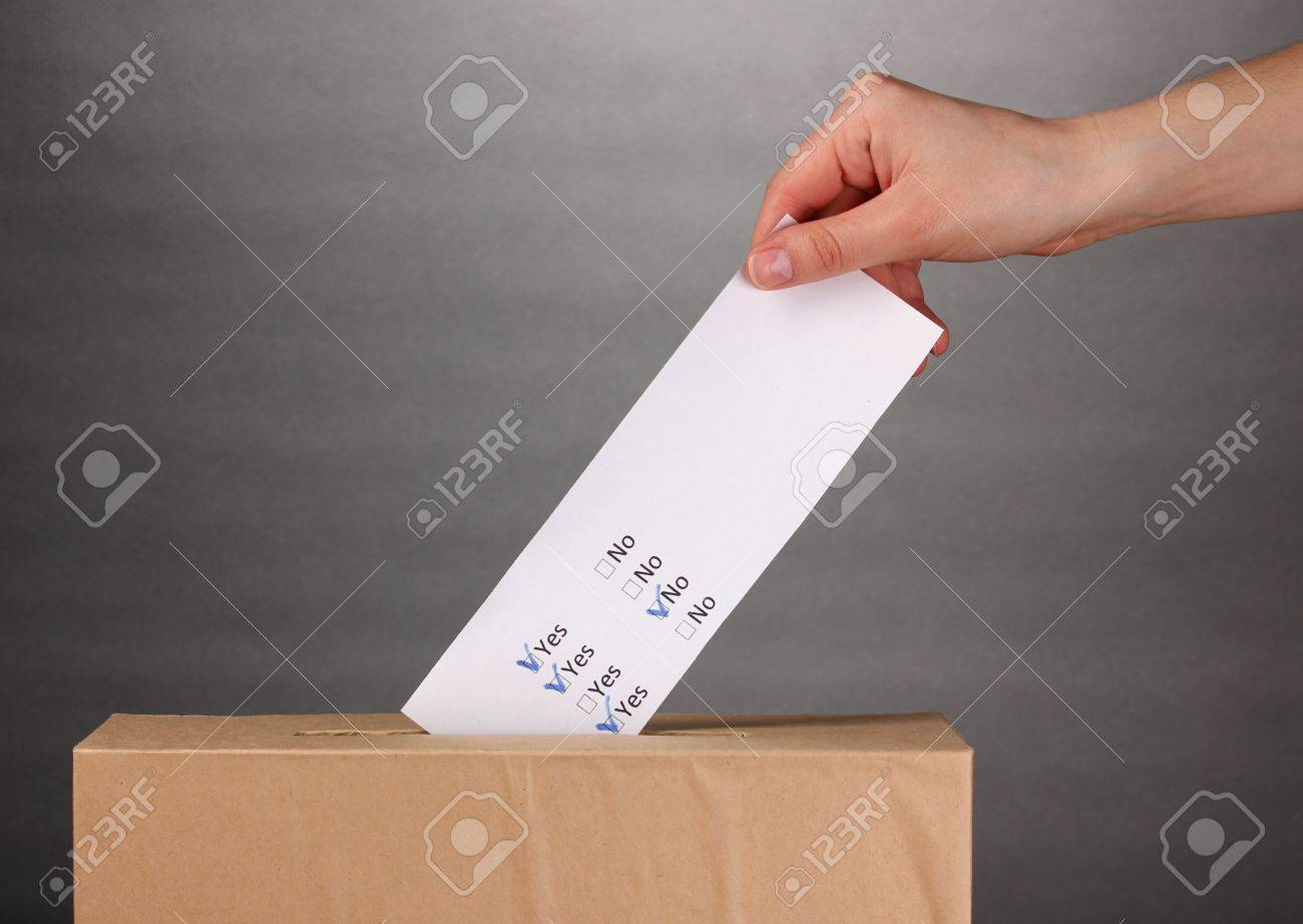 Hand with voting ballot and box on grey background Stock Photo - 13580232
