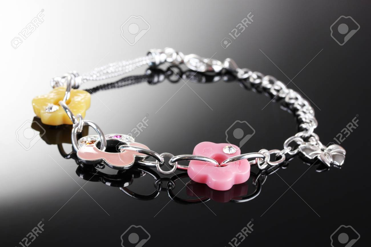 Beautiful silver bracelet with bright flowetrs on grey background Stock Photo - 13665742