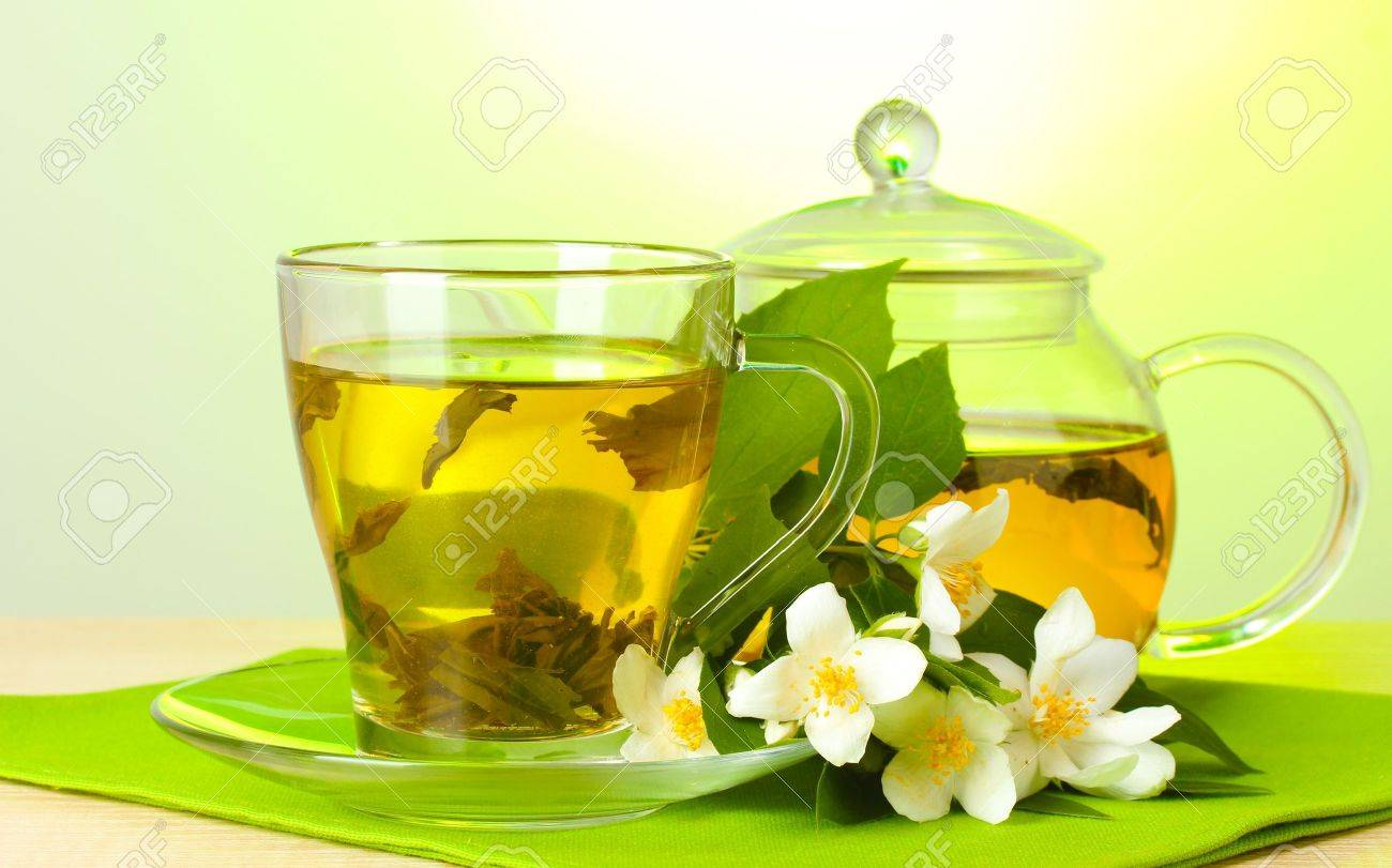 http://previews.123rf.com/images/serezniy/serezniy1205/serezniy120502592/13793478-green-tea-with-jasmine-in-cup-and-teapot-on-wooden-table-on-green-background-Stock-Photo.jpg