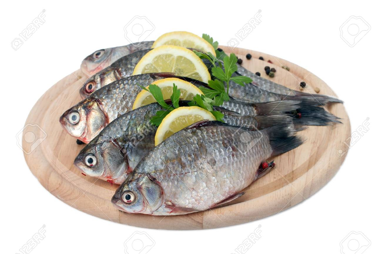 Fresh fishes with lemon, parsley and spice on wooden cutting board isolated on white Stock Photo - 13794287