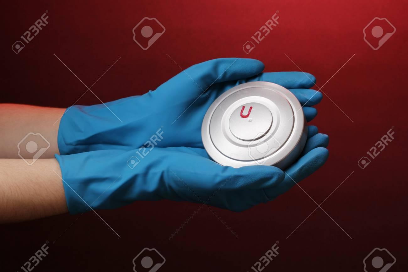 Uranium in hand on red background Stock Photo - 13865952