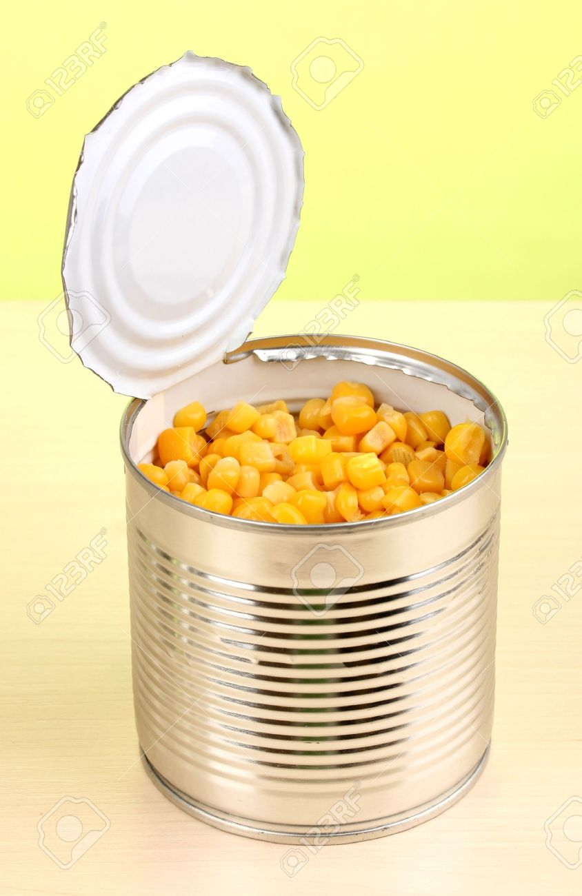 Open tin can of corn on wooden table on green background Stock Photo - 14069806