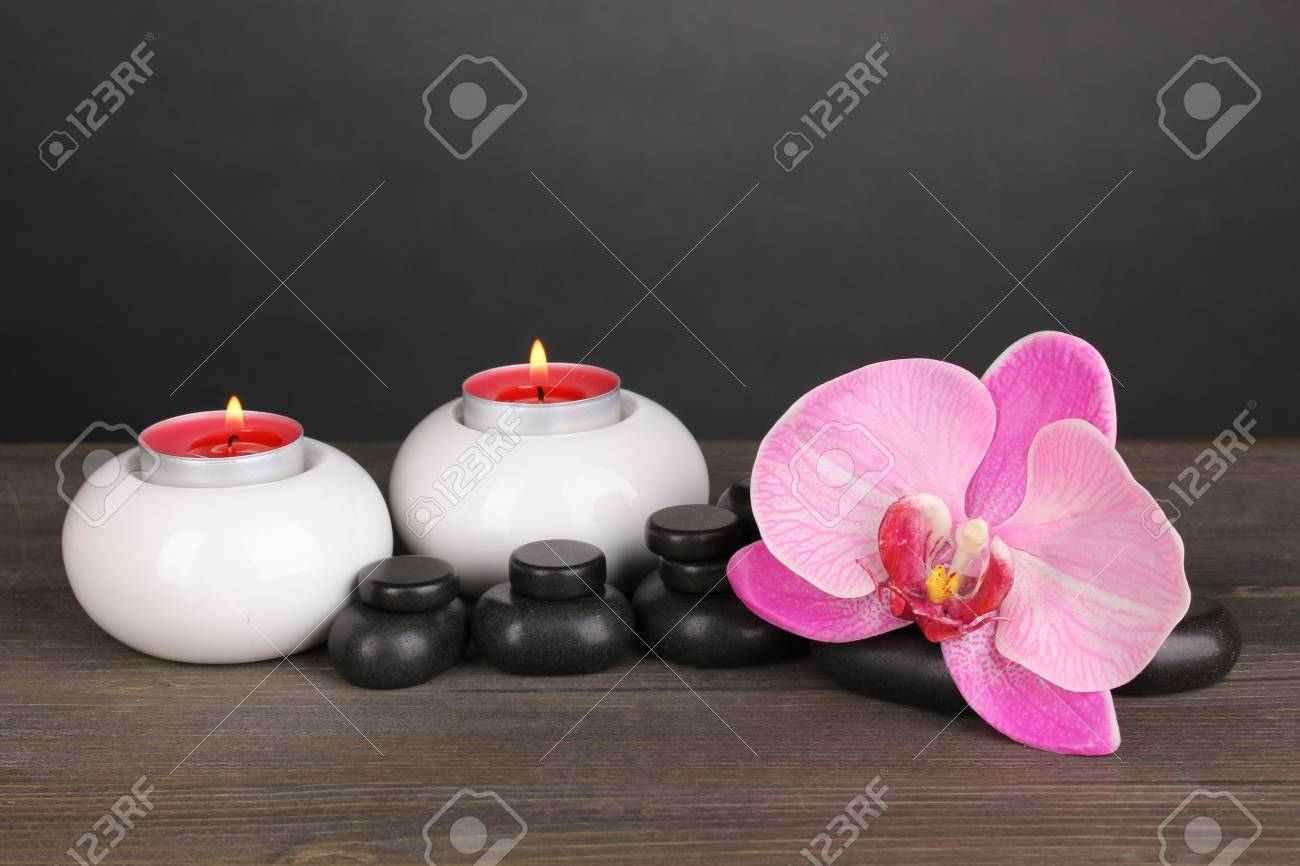 Spa stones with orchid flower and candles on wooden table on grey background Stock Photo - 14078019