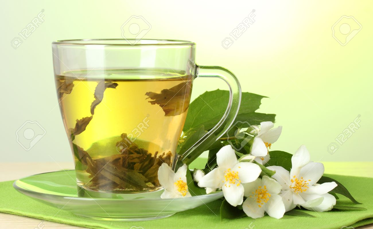 Cup Of Green Tea With Jasmine Flowers On Wooden Table On Green