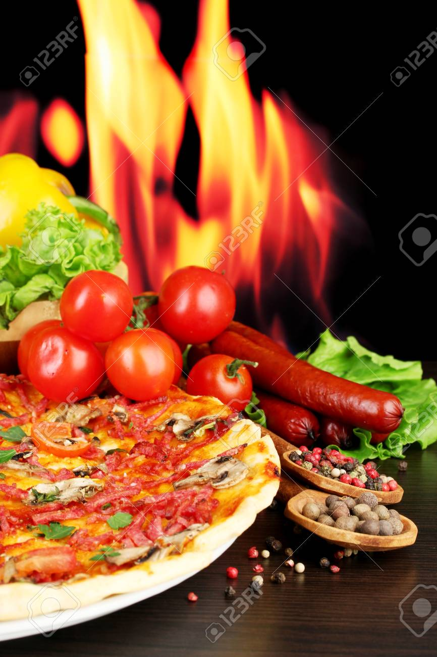 delicious pizza, salami, vegetables and spices on wooden table on flame background Stock Photo - 14111098