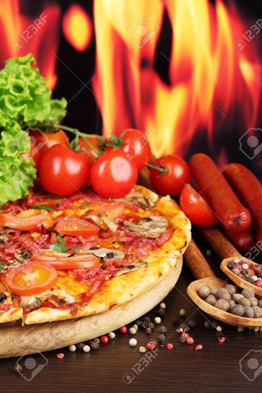 delicious pizza, salami, tomatoes and spices on wooden table on flame background Stock Photo - 14111412