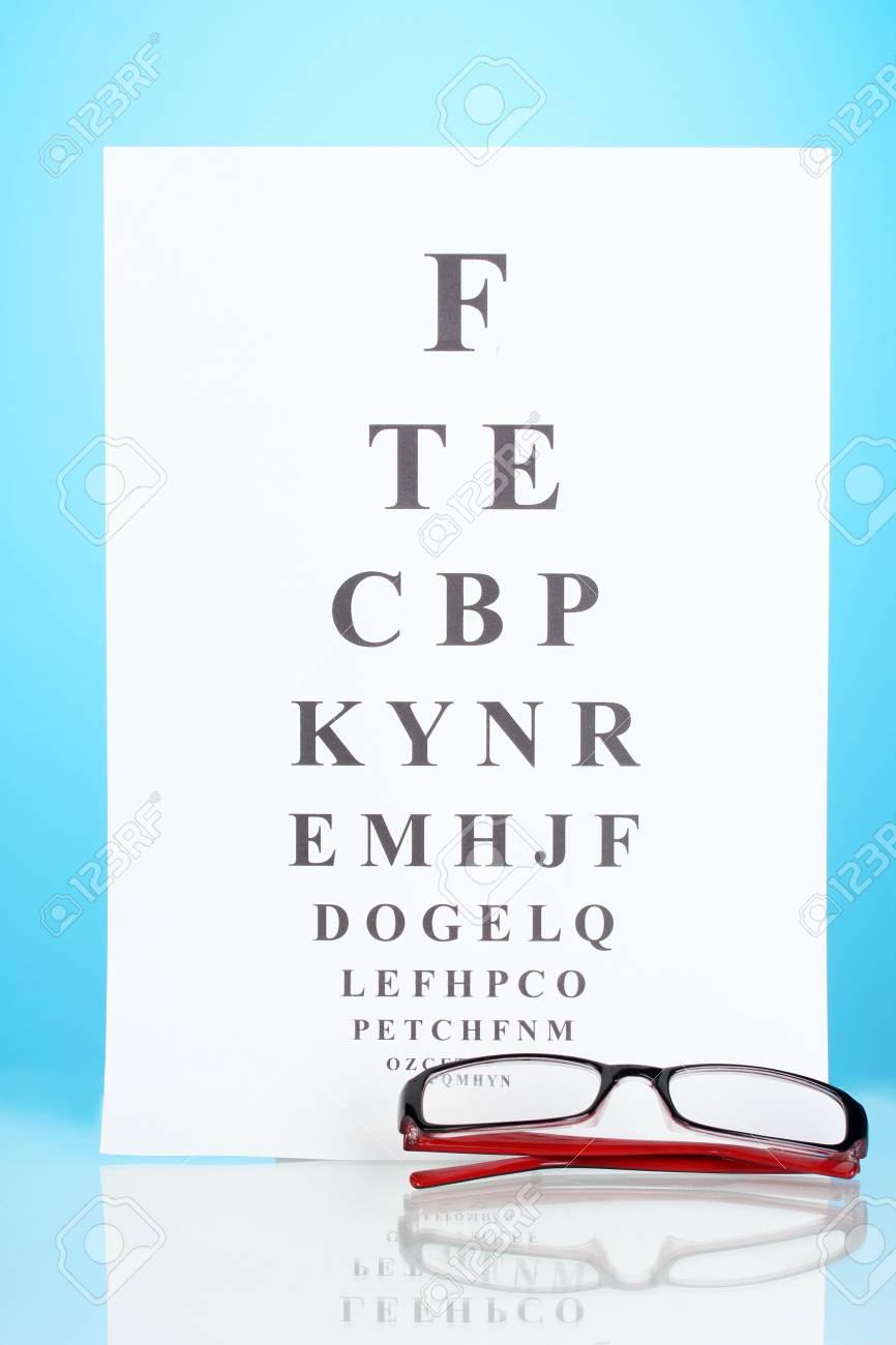 60c67d91c46 Eyesight test chart with glasses on blue background close-up Stock Photo -  14110546