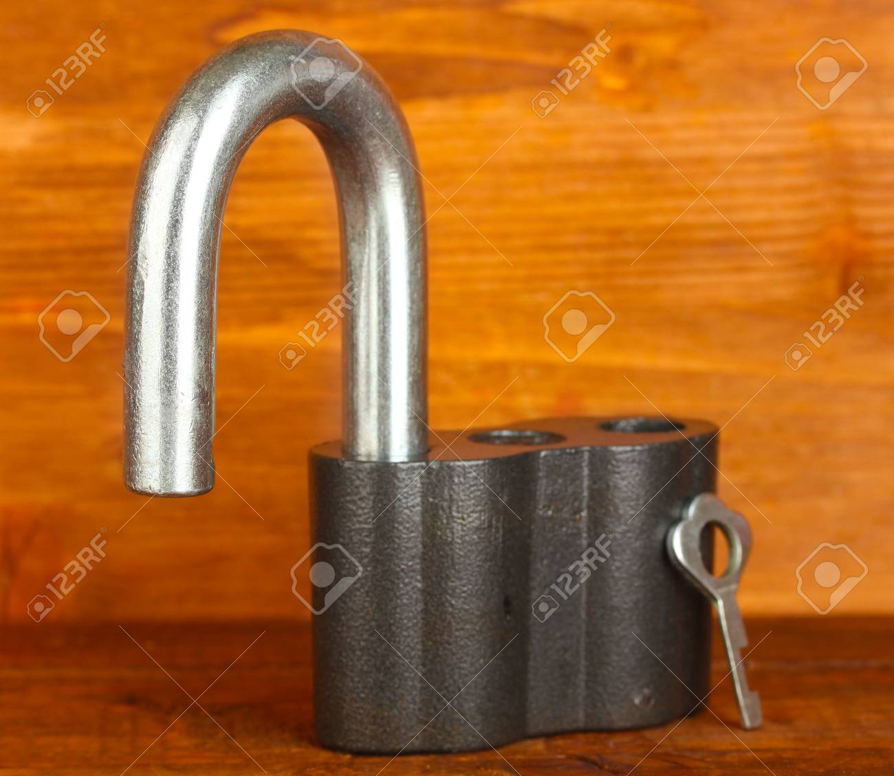 old padlock with key on wooden background close-up Stock Photo - 14110597