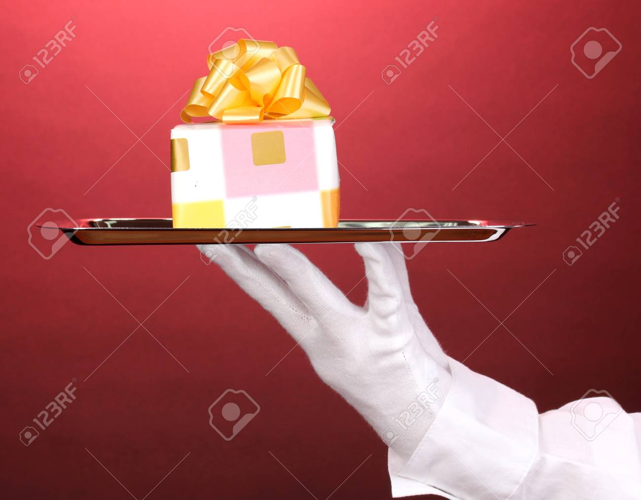Hand in glove holding silver tray with giftbox on red background Stock Photo - 14171111