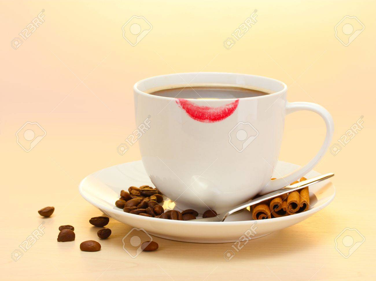 cup of coffee with lipstick mark beans and cinnamon sticks on wooden table Stock Photo - 14170096