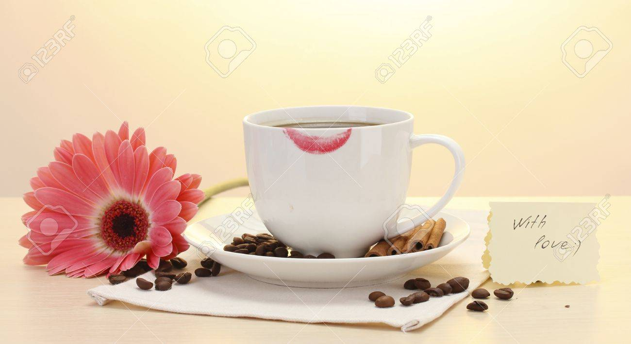 cup of coffee with lipstick mark and gerbera beans, cinnamon sticks on wooden table Stock Photo - 14367642