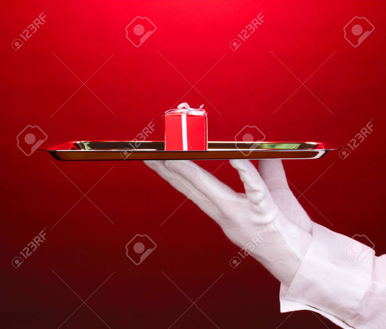Hand in glove holding silver tray with giftbox on red background Stock Photo - 14539682