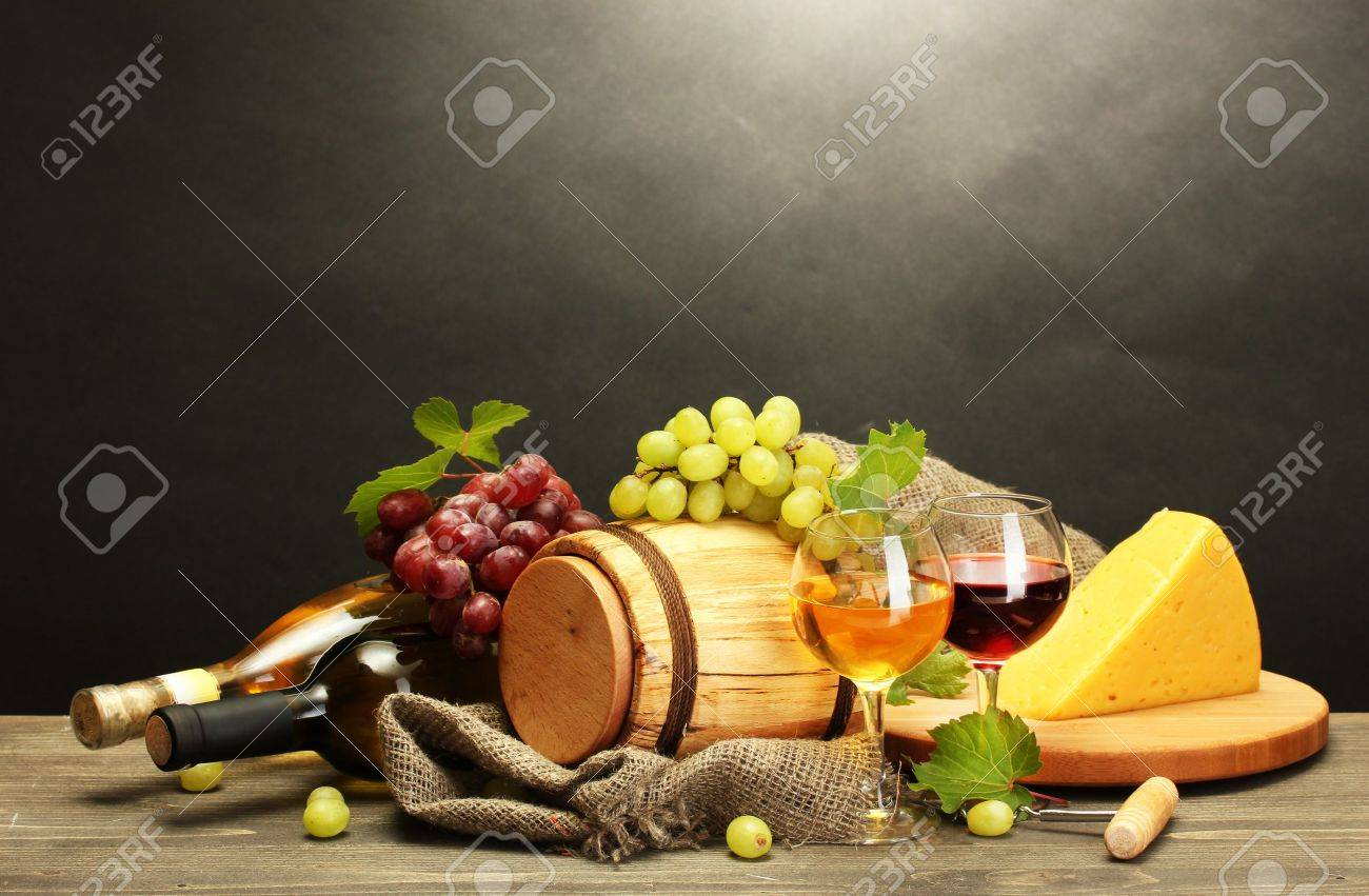 barrel, bottles and glasses of wine, cheese and ripe grapes on wooden table on grey background Stock Photo - 14838134