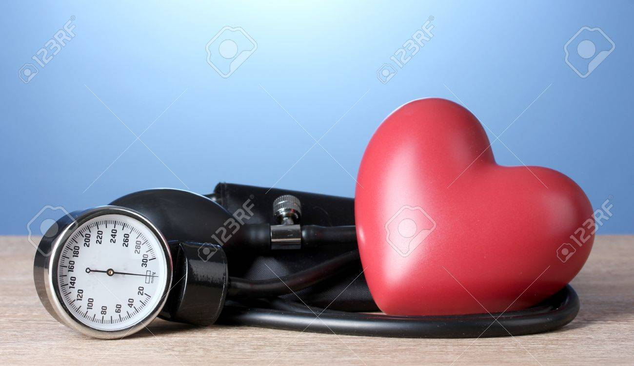 Black tonometer and heart on wooden table on blue background Stock Photo - 14954159