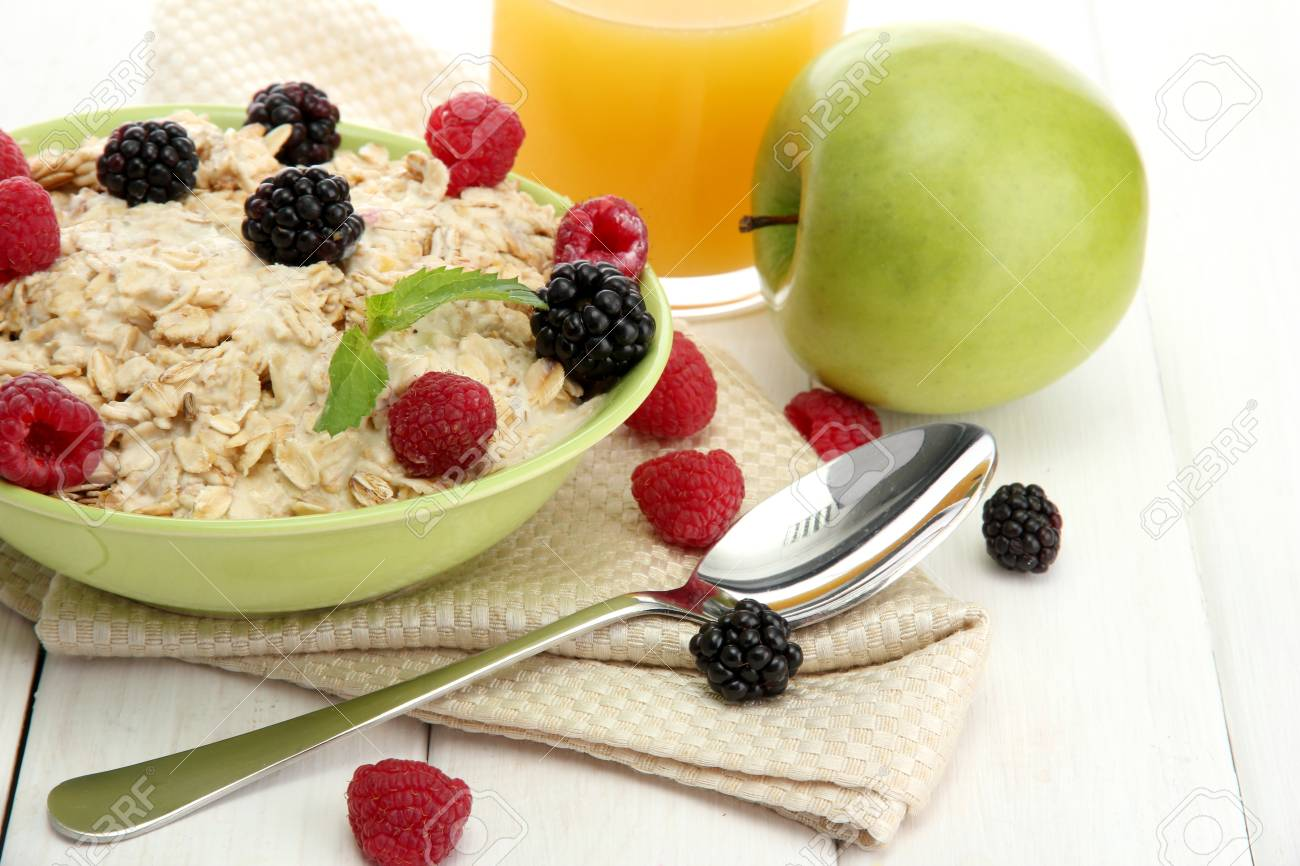 tasty oatmeal with berries and glass of juice, on white wooden table Stock Photo - 15410225