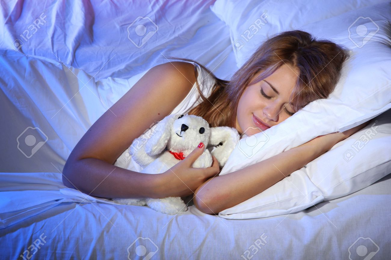 young beautiful woman with toy rabbit sleeping on bed in bedroom Stock Photo - 17187341