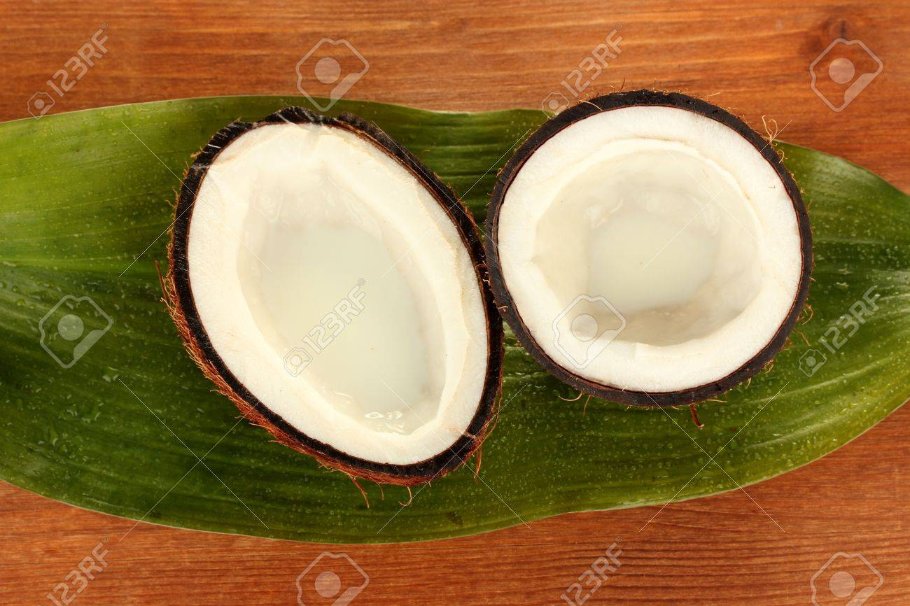 halves of coconut with green leaf on wooden background close-up Stock Photo - 15410273