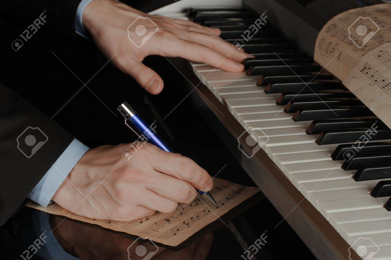 man hands playing piano and writes on parer for notes Stock Photo - 15421642