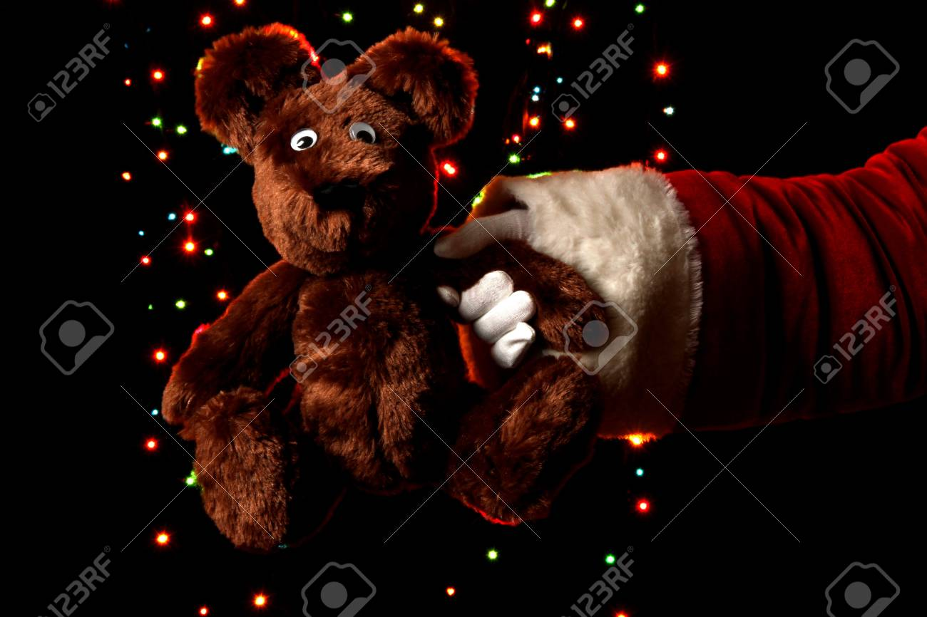 Santa Claus hand holding toy bear on bright background Stock Photo - 15426006