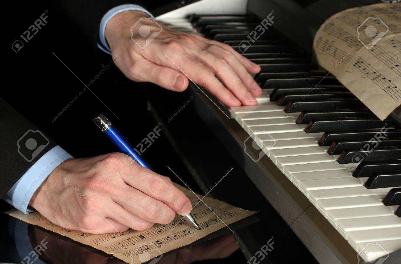 man hands playing piano and writes on parer for notes Stock Photo - 15457648