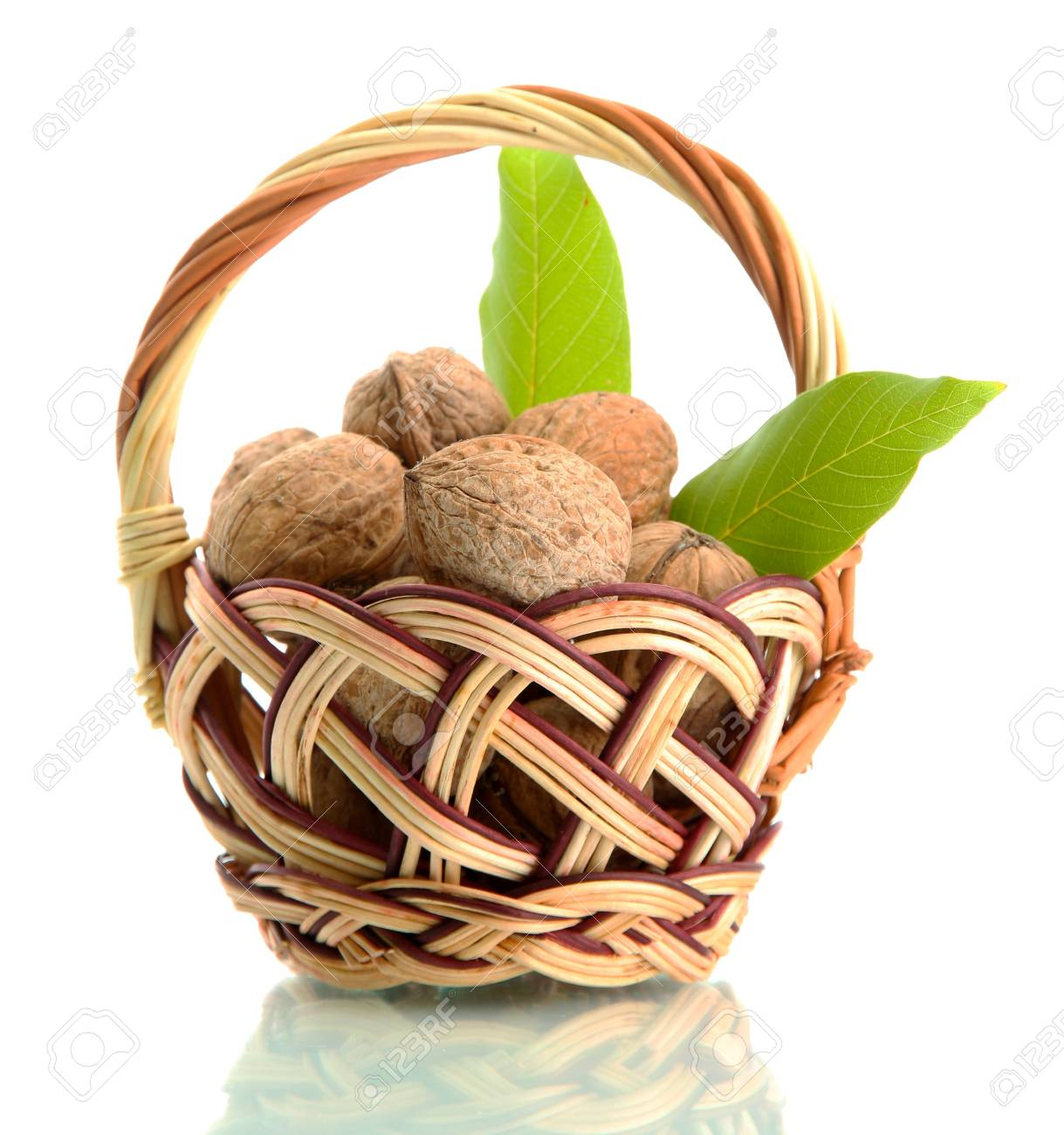 walnuts with green leaves in basket, isolated on white Stock Photo - 15546188