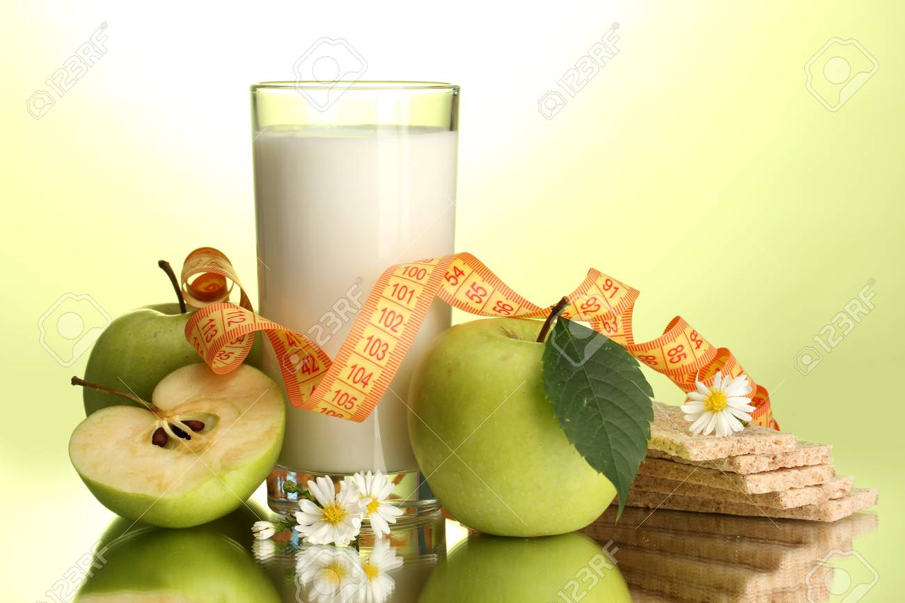 Glass of kefir, apples, crispbreads and measuring tape, on green background Stock Photo - 15563733