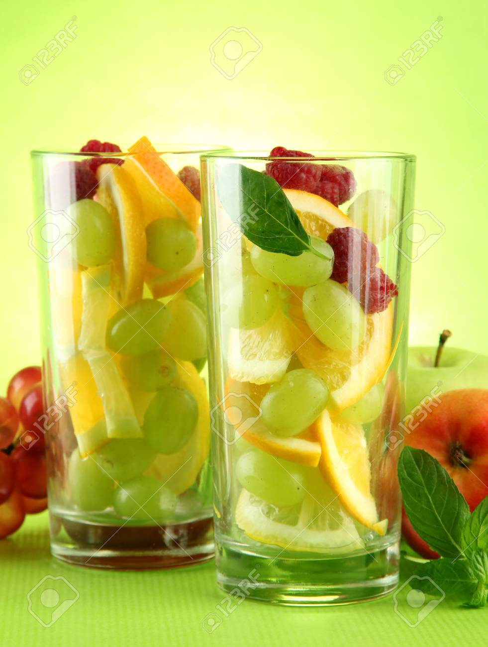 transparent glasses with citrus fruits, on grren background Stock Photo - 15643427