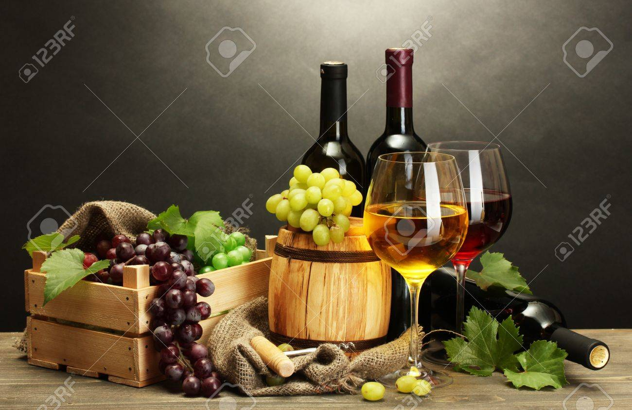 barrel, bottles and glasses of wine and ripe grapes on wooden table on grey background Stock Photo - 15690121