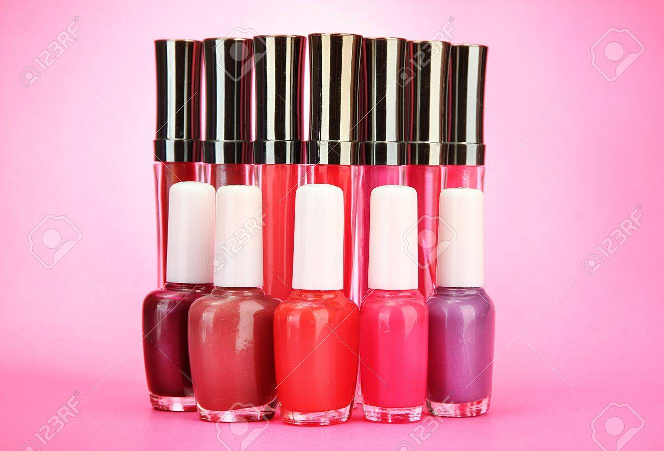 beautiful lip glosses and nail polish bottles, on pink background Stock Photo - 15690117