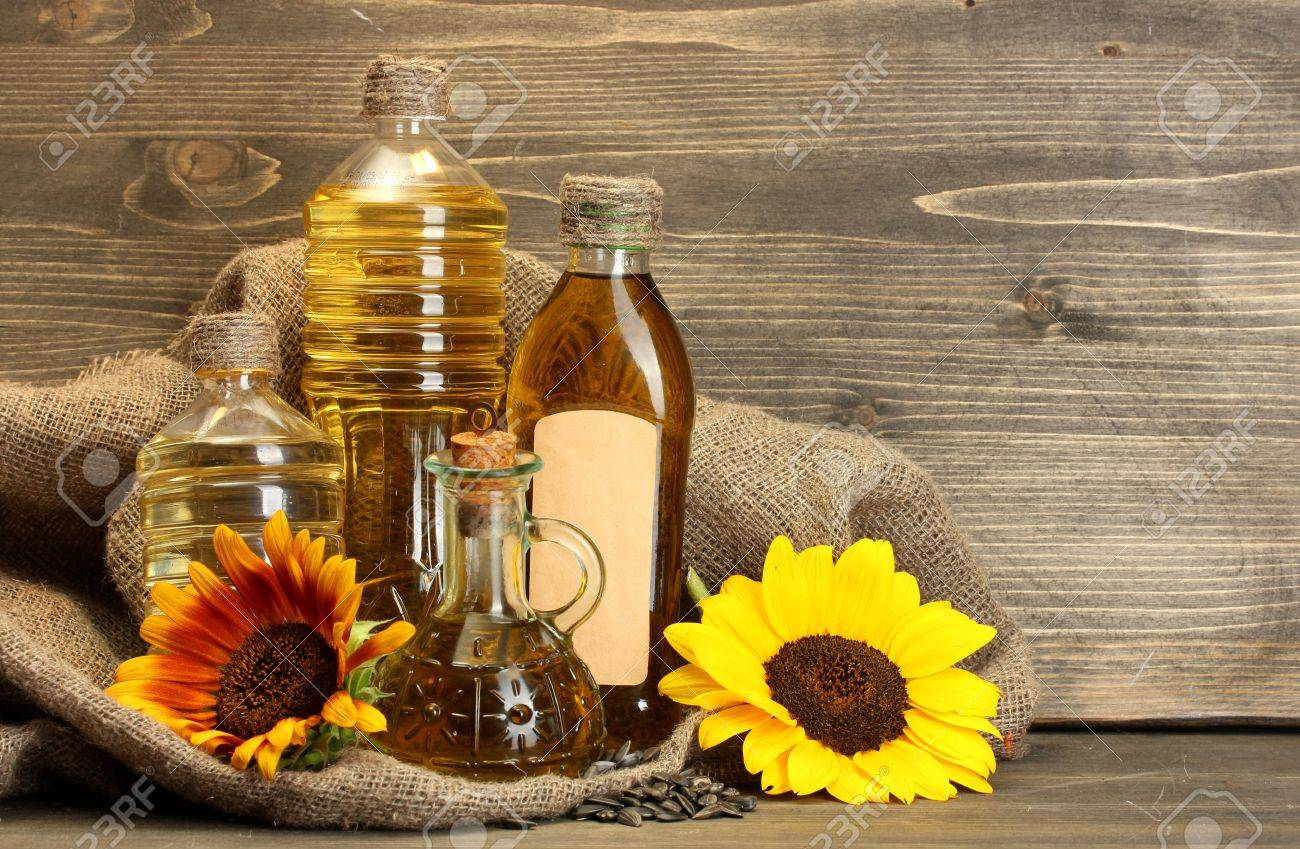 oil in bottles, sunflowers and seeds, on wooden background Stock Photo - 15729751