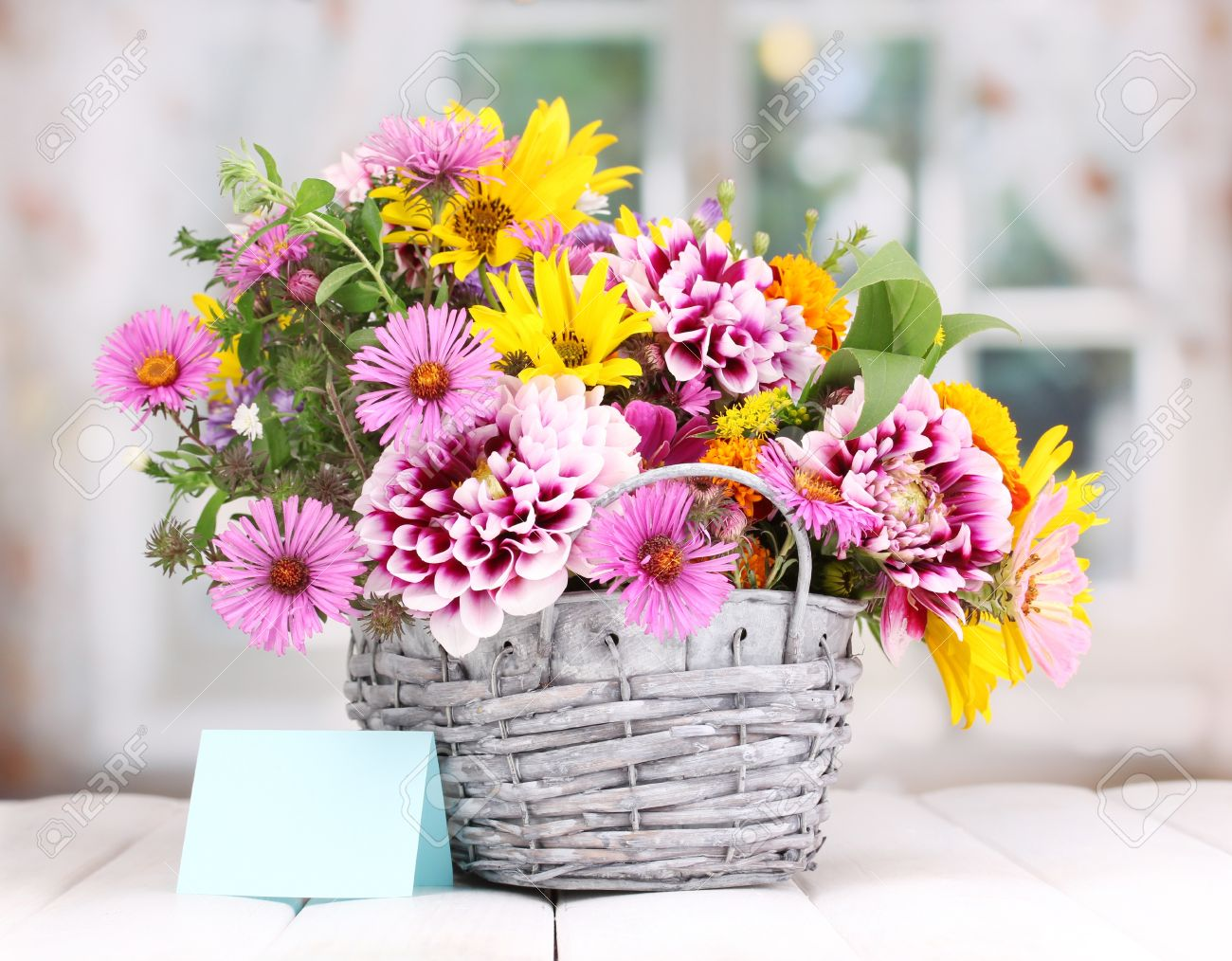 Beautiful Bouquet Of Bright Flowers In Basket On Wooden Table Stock