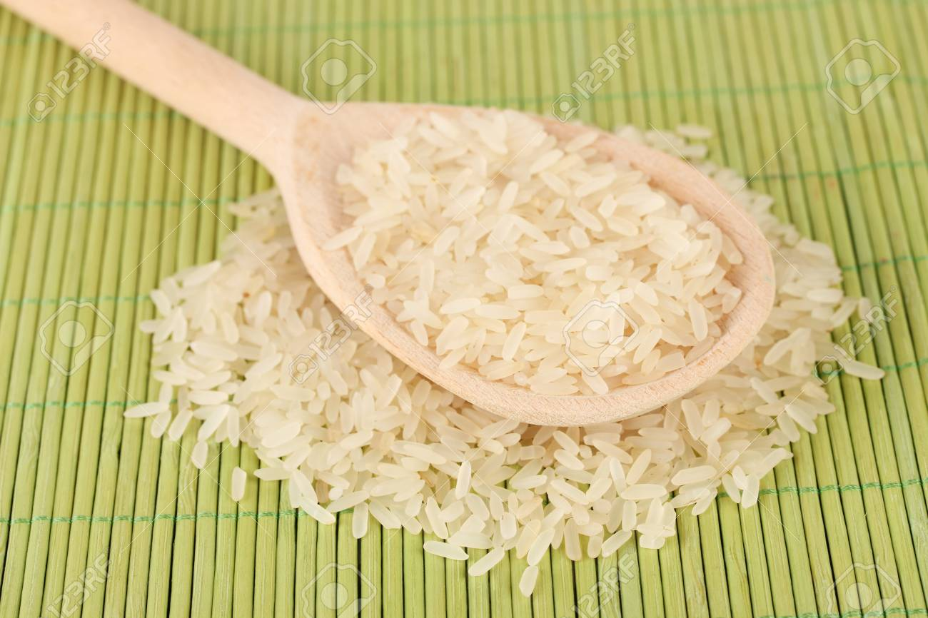 rice  in wooden  spoon on bamboo mat Stock Photo - 15938228