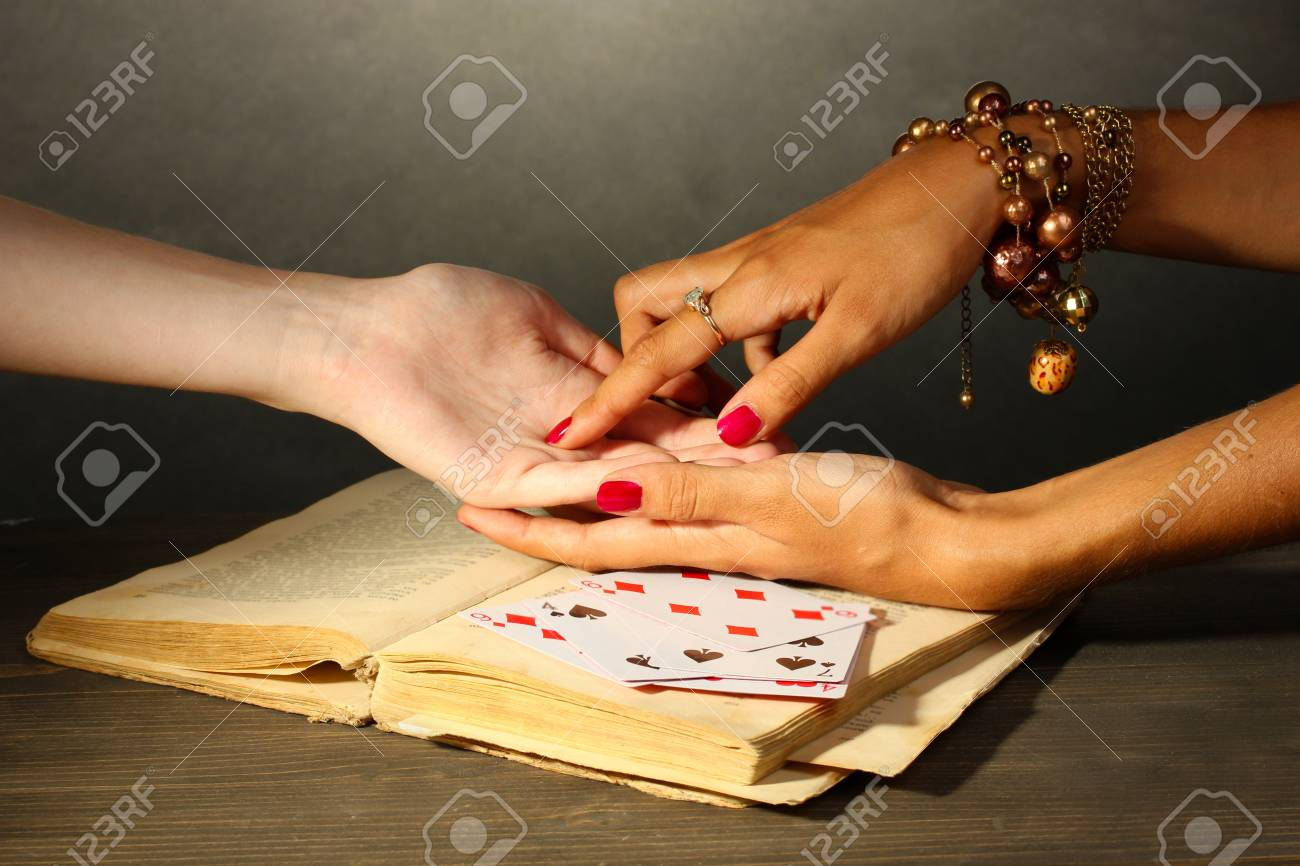 reading the lines hand in a woman's hands on grey backcground Stock Photo - 15994897