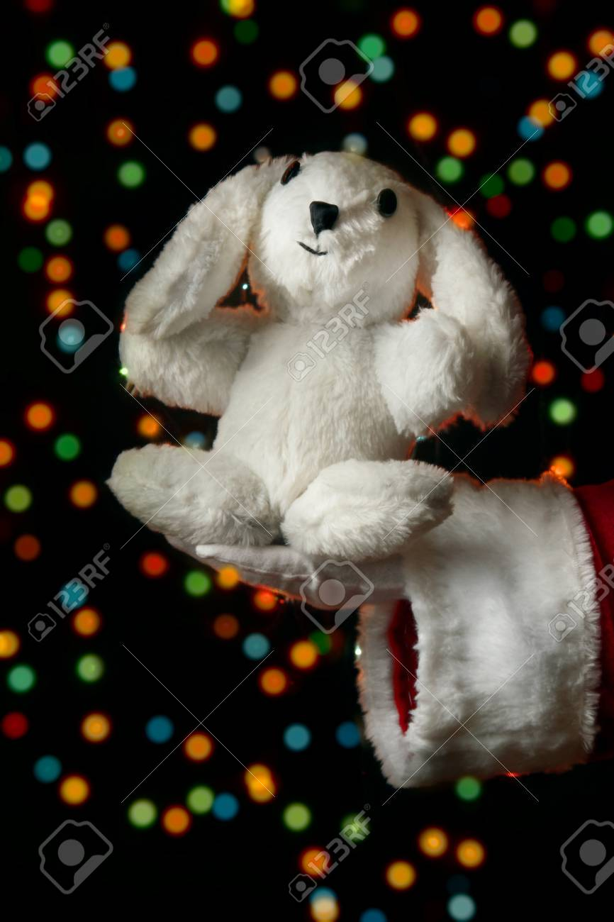 Santa Claus hand holding toy rabbit on bright background Stock Photo - 16106080