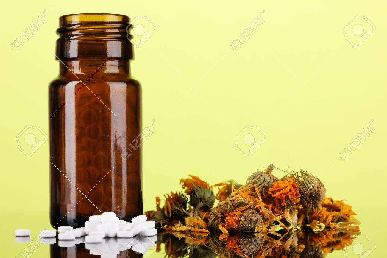 bottle with pills and herbs on green background. concept of homeopathy Stock Photo - 16106961