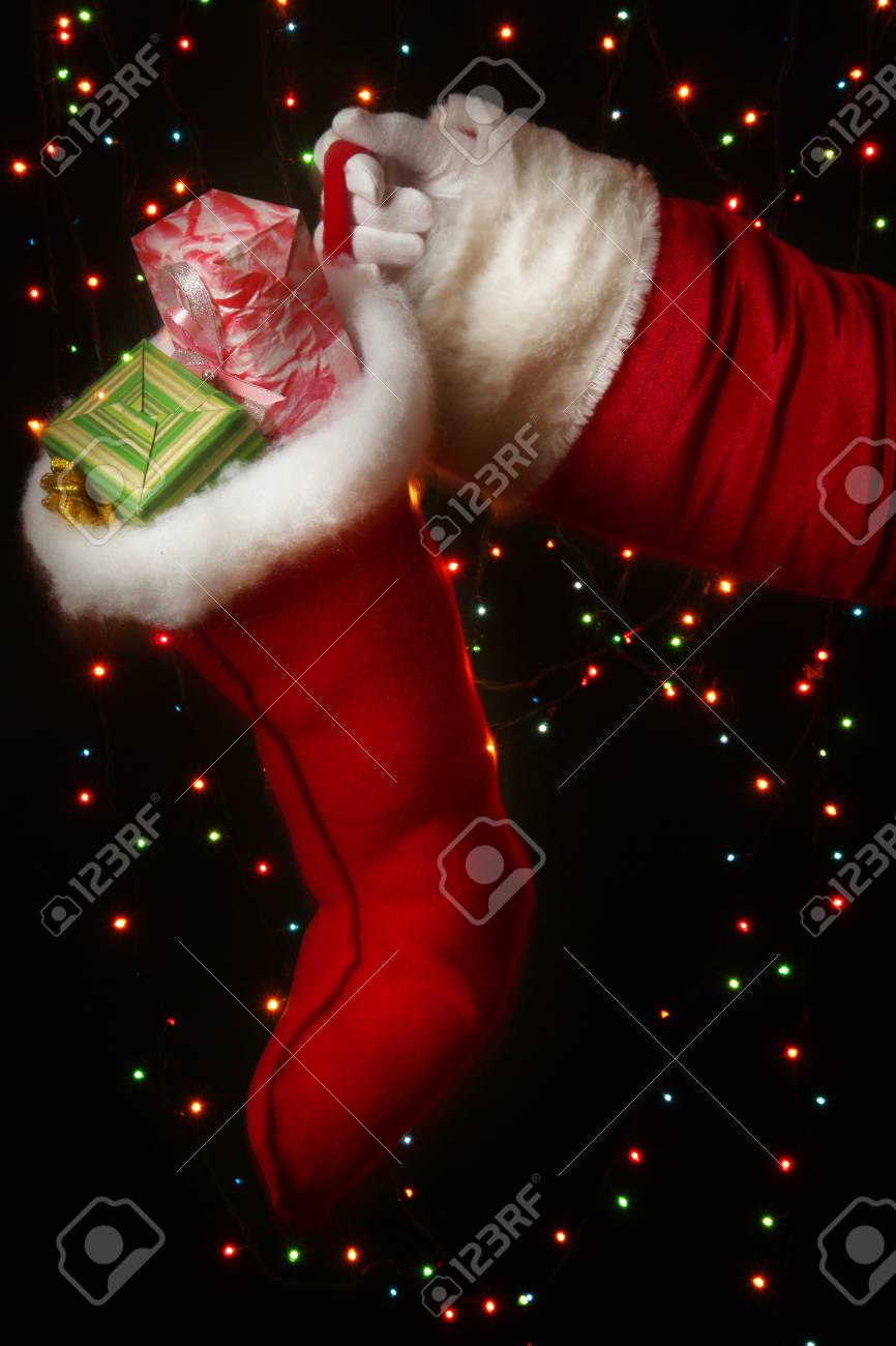 Santa Claus hand holding gifts on bright background Stock Photo - 16106956